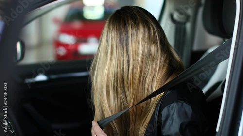 Young woman fastening seat belt