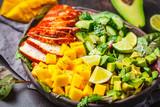 Grilled chicken, mango and avocado salad in dark dish on dark background. - 244311394