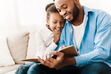 Little girl and father enjoying reading book together - 244326772