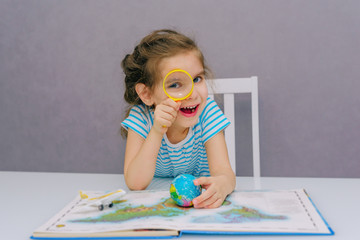 Little happy girl baby gets acquainted with the wild world of animals through the game, studying their habitat on the world map, looking through a magnifier magnifier. Home family education of childre