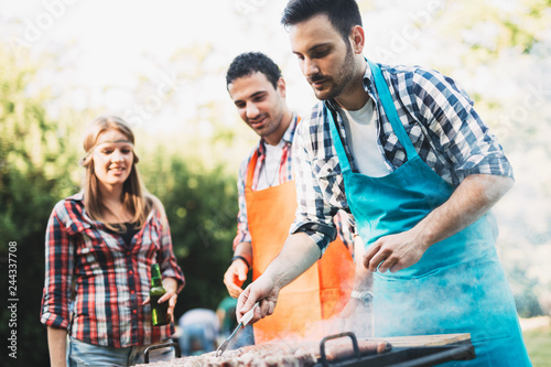 Young people grilling outdoors and smiling happy