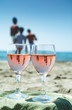 Quadro Young people on beach party with sea view, romantic celebration on sunny sandy beach, two glasses with rose wine with reflection