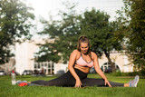 Young tired plus size woman in pink sporty top and leggings trying sit on twine on yoga mat while spending time in city park - 244349171
