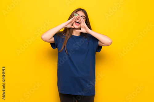 Leinwandbild Motiv Young woman with glasses over yellow wall shouting and announcing something