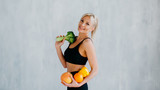 sports woman holding fresh fruits and vegetables in hands, healthy eating concept