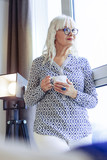 Positive good looking woman drinking coffee at home - 244359579