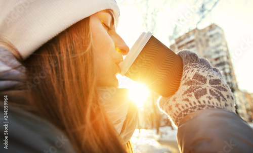 Young woman drinks coffee from the paper cup in the winter park