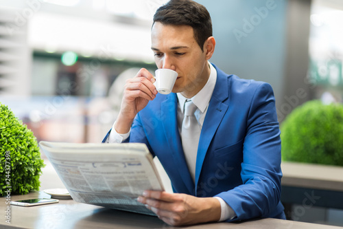 Young manager having a coffee and reading a newspaper