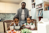 Caring loving father giving breakfast for his beautiful twins - 244382154