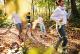 Small group of people running in woods in the autumn. - 244391518