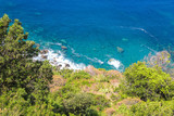 View of the tropical plants with the blue Mediterranean Sea in the a background on a bright sunny day. - 244400346