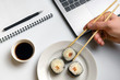 Break time for sushi eating. Sushi rolls snacking at work. Laptop and notebook on white organized desk.