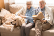 Portrait of happy senior couple sitting on couch with pet dog and reading books enjoying weekend at home in retirement