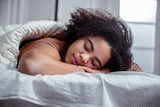 Peaceful dark-skinned woman resting on bed and having nice sleep - 244445789