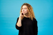Portrait of thoughtful attractive redhead curly girl looking at camera dressed in black sweater on blue background.