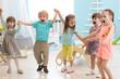 Leinwandbild Motiv Group of happy kindergarten children jumping raising hands while having fun in entertainment center