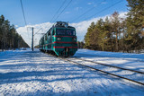 Snowy landscape with railway and a train. Winter forest and blue sky. Beautiful morning in the forest.