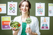 Portrait of a woman dietitian in medical gown standing with salad on the green wall background with drawings on a topic of healthy food indoors