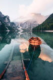On the pier. Wooden boat on the crystal lake with majestic mountain behind. Reflection in the water - 244471355