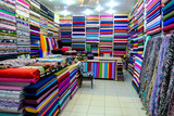 Rolls of fabric and textiles for sale stacked on shelves in shop,View of cloth rolls of different colors and patterns on shelves in fabric store