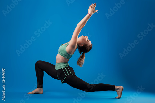 fototapeta na ścianę young beautiful dancer posing on isolated blue studio background