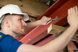 Construction Worker Fitting Steel Support Beam Into Renovated House Ceiling - 244499185