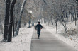 Young man running in city park at cold winter day.