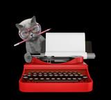 Fototapeta Koty - Cute cat is typing on a typewriter keyboard. Isolated on black © helga1981