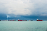 View of the Singapore Strait from Sentosa Island. Ships, industrial landscape and stormy weather. - 244527739