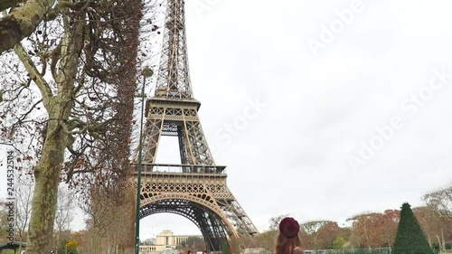 Wall mural Young girl with long hair, red lipstick and beret walking and smiling on the Eiffel tower background