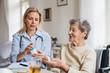 Leinwandbild Motiv A health visitor explaining a senior woman in wheelchair how to take pills.