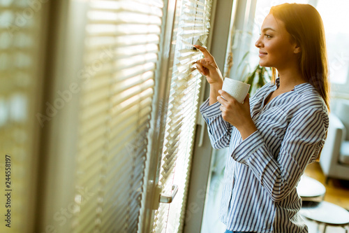 Attractive young woman holding cup with hot tea or coffee and looking at the sunrise standing near the window in room
