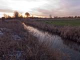 Abendstimmung an einem Bach im Norden von Deutschland. An Ufer liegt etwas Schnee und das trockene Gras spiegelt sich im Wasser. - 244561760