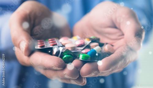 Leinwanddruck Bild Pills in human hands, close-up view