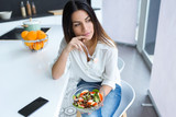 Pretty young woman eating salad while sitting on a chair in the kitchen at home. - 244572570