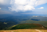 view from peak of mountain on the hills and rainy blue and gray clouds on the horrizon - 244573167