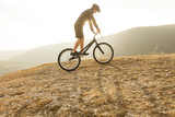 Young athlete on bicycle in countryside - 244574363