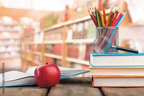 Leinwandbild Motiv Stack of colorful books and fresh apple