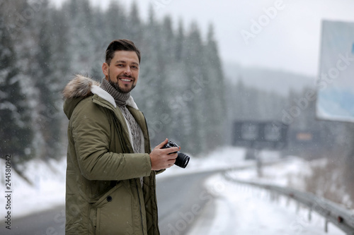 Leinwandbild Motiv Male photographer with camera on snowy road, space for text. Winter vacation
