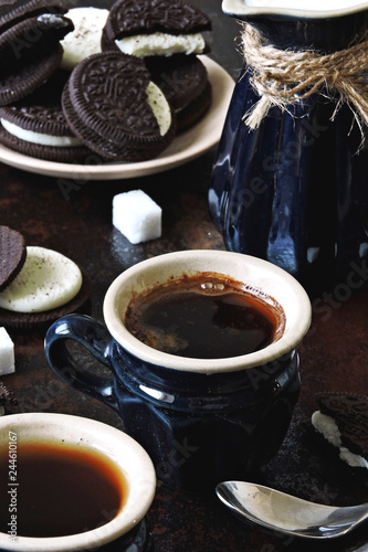 Two cups of espresso, a jug of milk and chocolate chip cookies with a white filling. Stylish shabby background. Coffee breakfast for two.