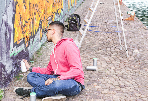 Street artist painting colorful graffiti on a wall under the bridge - Urban man performing with murales - Concept of modern contemporary art - 244628160