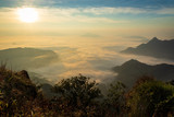 sunrise over mountain and fog with grass foreground at chiang Rai, Thailand