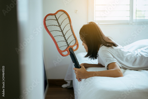 Asian woman using mosquito swatter at home,Female with mosquito electric net racket in bedroom - 244641503