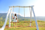 Happy young woman relaxing by swing on hillside at morning sunrise. - 244662705