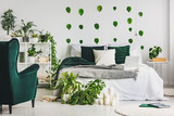 Urban jungle in cozy emerald green and white bedroom interior with king size bed - 244686306