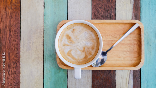 Coffee in a white cup and chocolate cake on a wooden table