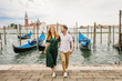 Young beautiful couple girl in a green dress a man in a white shirt walk near the water overlooking the Grand Canal in Venice Italy