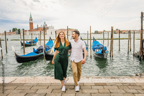 fototapeta na ścianę Young beautiful couple girl in a green dress a man in a white shirt walk near the water overlooking the Grand Canal in Venice Italy