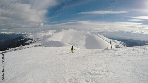 fototapeta na ścianę A girl rides a snowboard in the mountains. Lots of snow. Carpathians. Ski jacket and trousers.