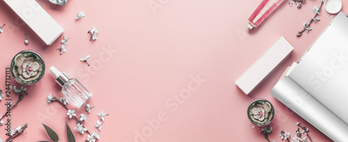 Pastel pink beauty desktop background with open magazine mock up, modern cosmetics and blossom branches, top view. Fashion blog and female business concept. Flat lay frame . Banner or template